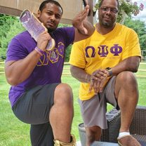Willie Owens and his son Devan proudly don the purple and gold of Omega Psi Phi.